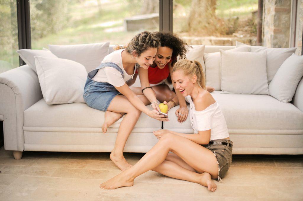 Gruppo di ragazze sorridenti che guardano il telefono