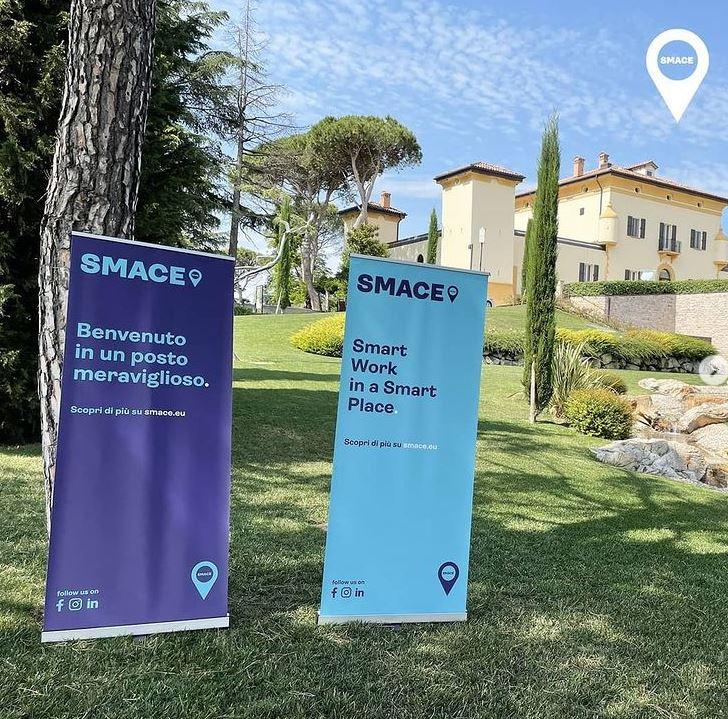 Paesaggio naturale con due cartelloni di Smace dedicati allo smartworking